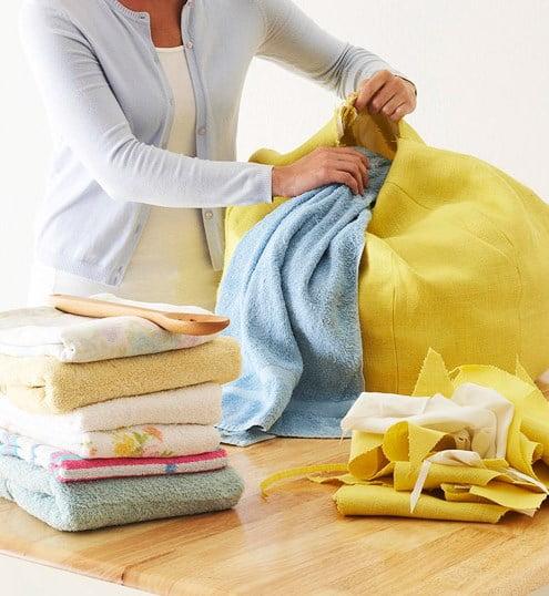 """Depois que todas as laterais estiverem juntas, tire o puff do avesso e comece a preencher o """"recheio"""". No caso, da base até o meio, é necessário preenchê-lo com tecidos resistentes (como toalhas velhas, cobertas velhas, retalhos, etc.) para dar suporte."""