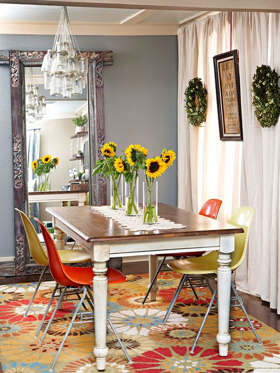 Sala de jantar com mesa rústica (provando que nem sempre móveis velhos devem ser descartados) com cadeiras de plástico coloridas e girassóis! Para completar o charme da sala, um lustre feito com potes de vidro! :)